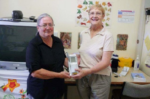Anne Kidd accepts the I-Stat machine from Carolyn Gorringe